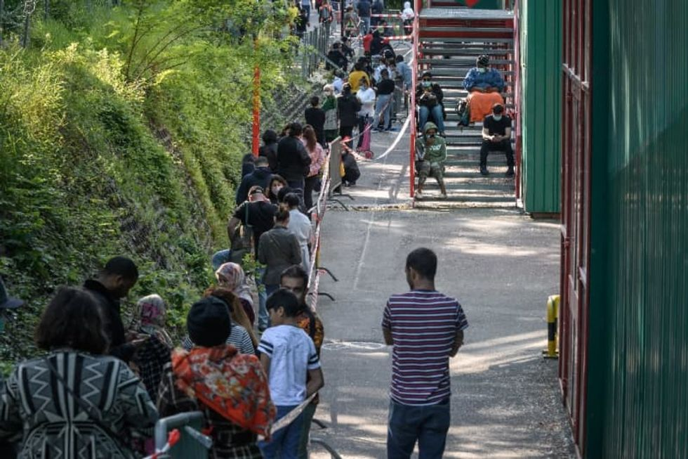 Crisis lays bare poverty in Geneva, as thousands queue for food