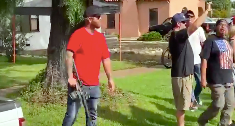 WATCH: Man jumps out of pickup to point rifle at protesters confronting Trump supporters
