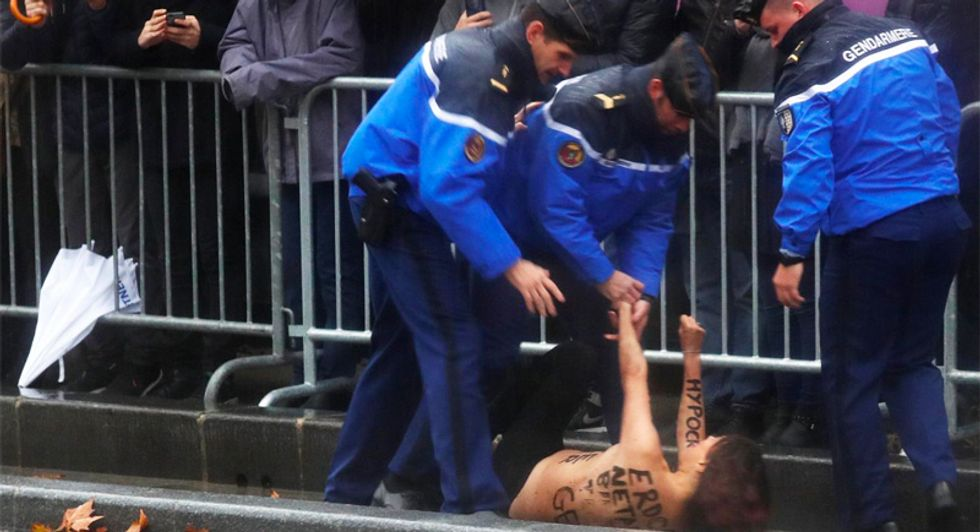 Topless female protester with 'Fake  Peacemaker' scrawled on her chest runs at Trump's motorcade in Paris
