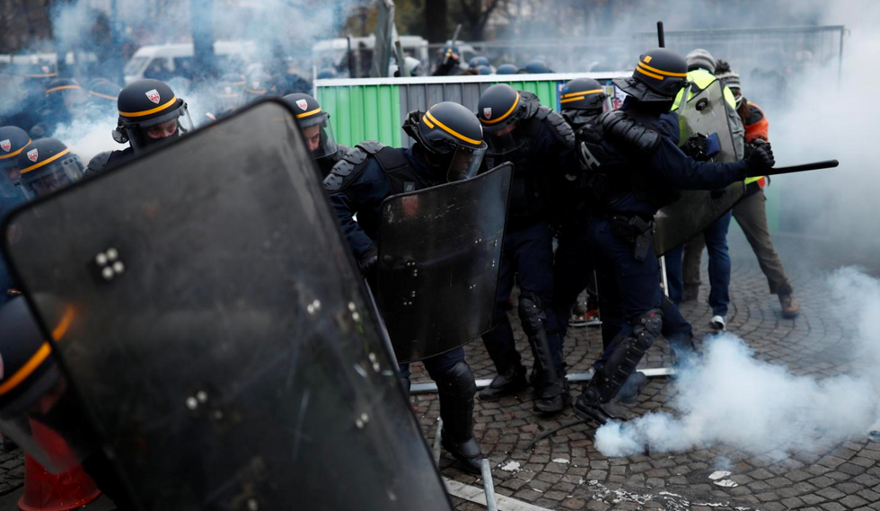 French police fire tear gas and use water cannons on protesters on Champs Elysees
