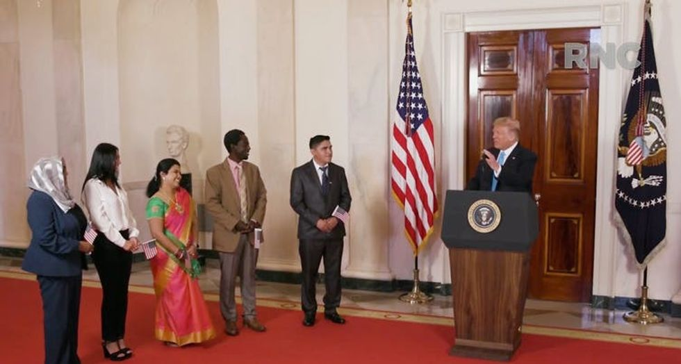 Trump stands with five new US citizens, with American flag in the background
