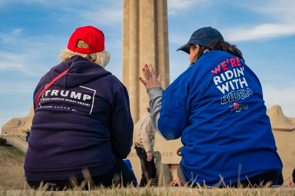 Two women conversing with their backs to the camera, one wearing a Trump shirt and the other a Biden shirt.