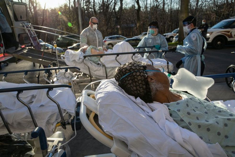Several patients on gurneys outside a hospital.