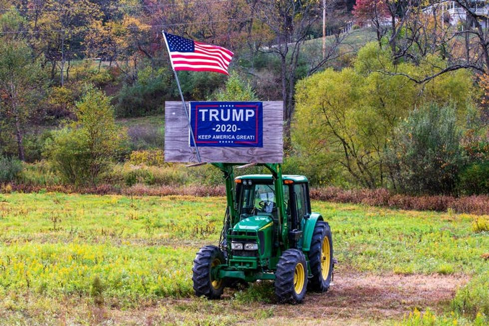 A Trump 2020 reelection sign and an American flag are displayed on a piece of farm equipment in Valley Township, Montour County, Pa.