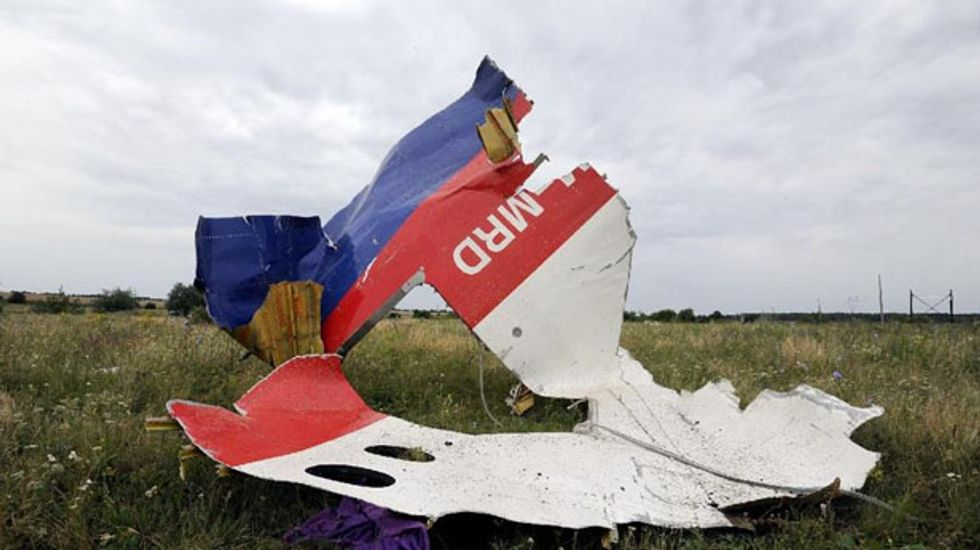 Authorities use scent hounds at MH17 wreckage site as war continues around them