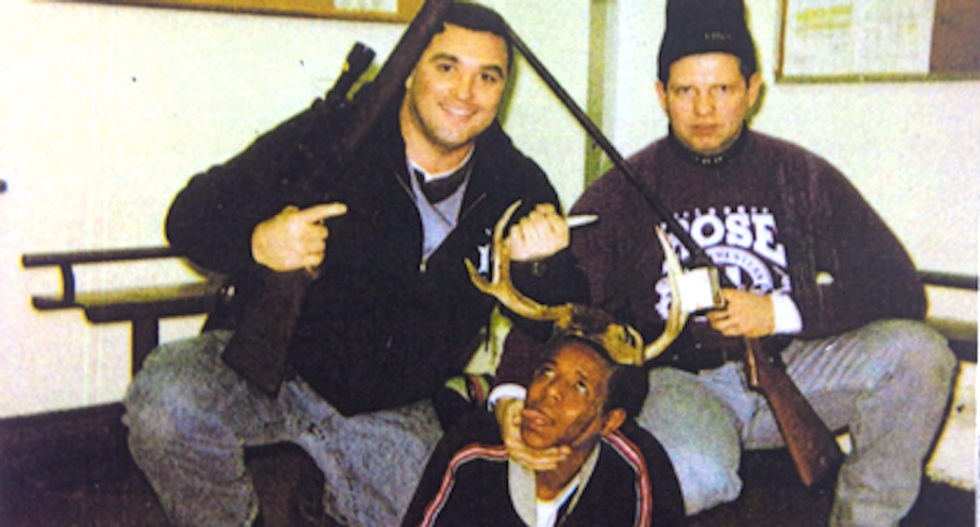 Photo shows rifle-toting Chicago cops posing with a black drug suspect like a hunting trophy