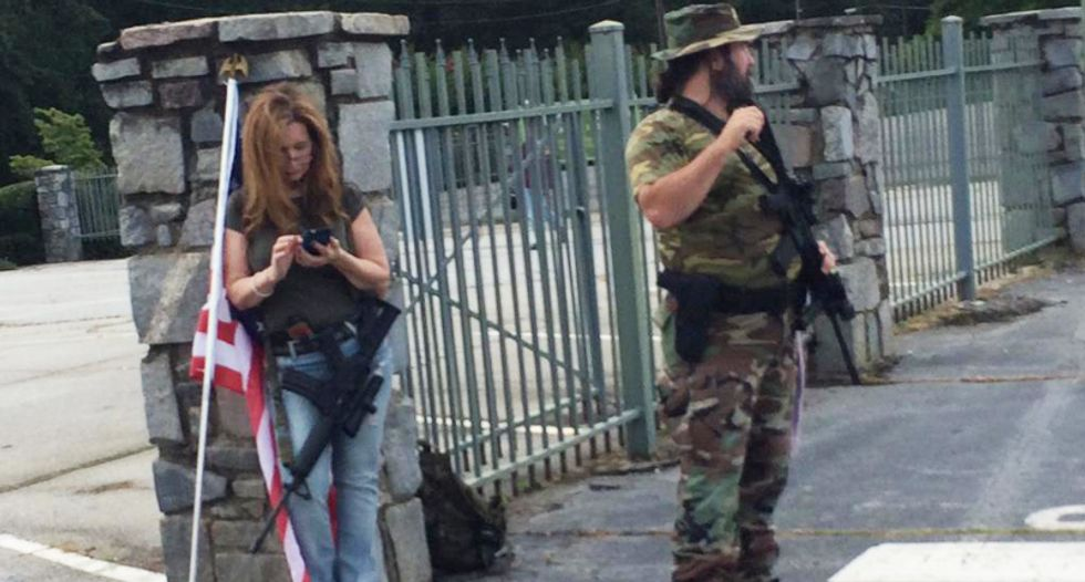 Armed militia members stand by as Confederate flag supporters descend upon Georgia park