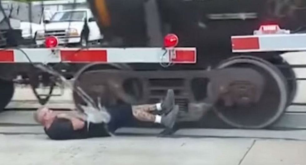 WATCH: Man defies death and rolls through wheels of moving freight train