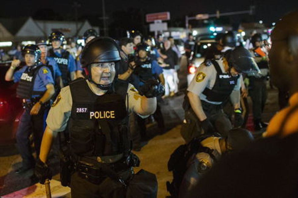 St Louis County police officers interact with anti-police demonstrators during protests in Ferguson, Missouri August 10, 2015.  REUTERS/Lucas Jackson