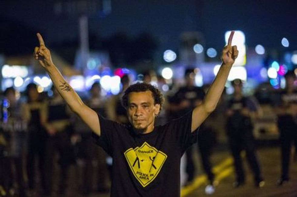 Demonstrators gesture at a line of St Louis County police officers during protests in Ferguson, Missouri August 11, 2015.  REUTERS/Lucas Jackson