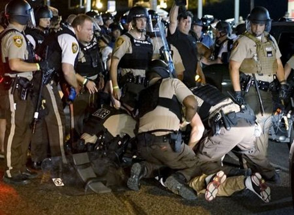 Police detain a protester in Ferguson, Missouri, August 10, 2015. REUTERS/Rick Wilking