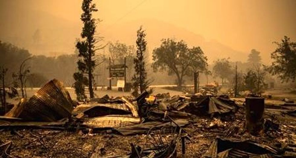 California wildfire jumps containment line, threatens forest homes