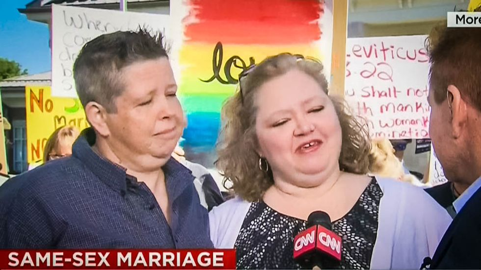 WATCH: Kim Davis' clerk issues marriage license to lesbians while Christians shout they are going to Hell