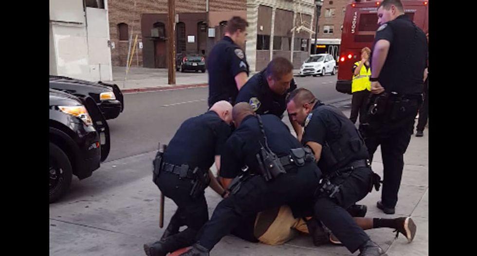 'He's a f*cking kid': Video shows nine California cops arrest sobbing black teen 'for jaywalking'