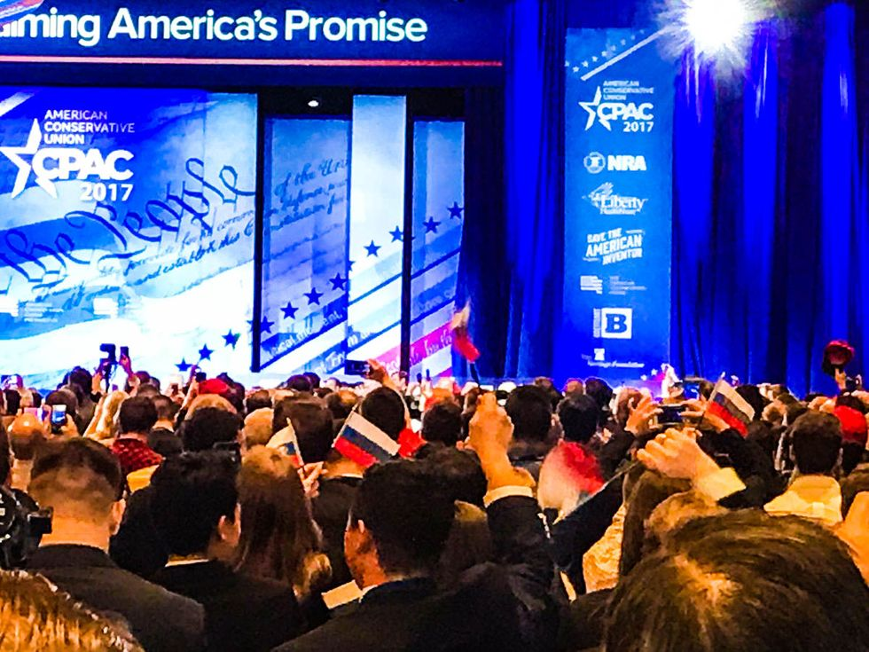 CPAC scrambles to control damage after attendees wave Russian flags during Trump speech