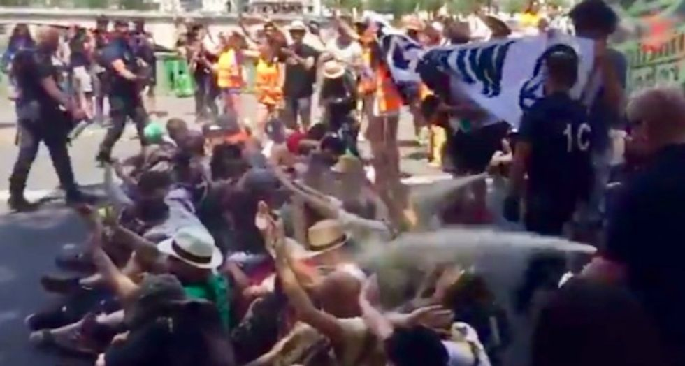 WATCH: On 'hottest day in history of France,' police tear-gas climate campaigners in Paris