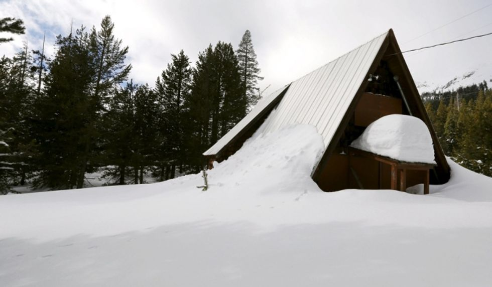 An above-average amount of snow covers a small cabin in Phillips, Calif., Dec. 30, 2015. (Reuters/Fred Greaves)