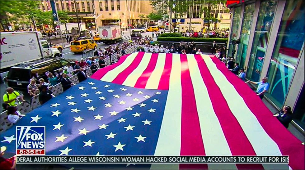 Fox & Friends hosts sit while flag is unfurled and military performs national anthem