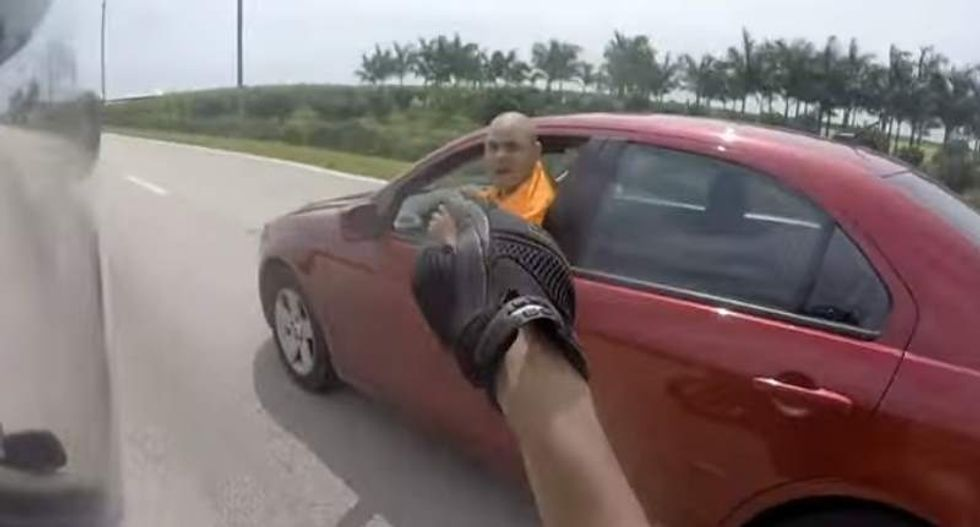 WATCH: Shouting road raging motorist tries to drive biker off the road