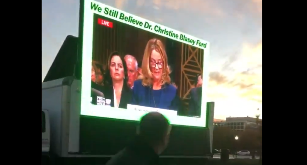 Protestors set up giant broadcast of Christine Blasey Ford's testimony as conservative lawyers gather to celebrate Kavanaugh