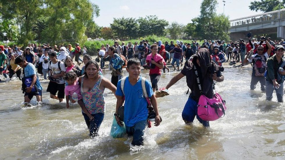 Troops fire tear gas as migrants try to storm into Mexico