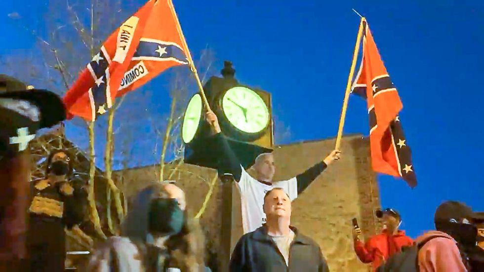 Group with Confederate flags confronts liberal voters as they march to the polls in North Carolina