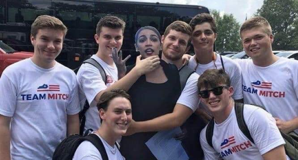 Young Mitch McConnell supporters pose for a photo strangling a cardboard cutout of AOC