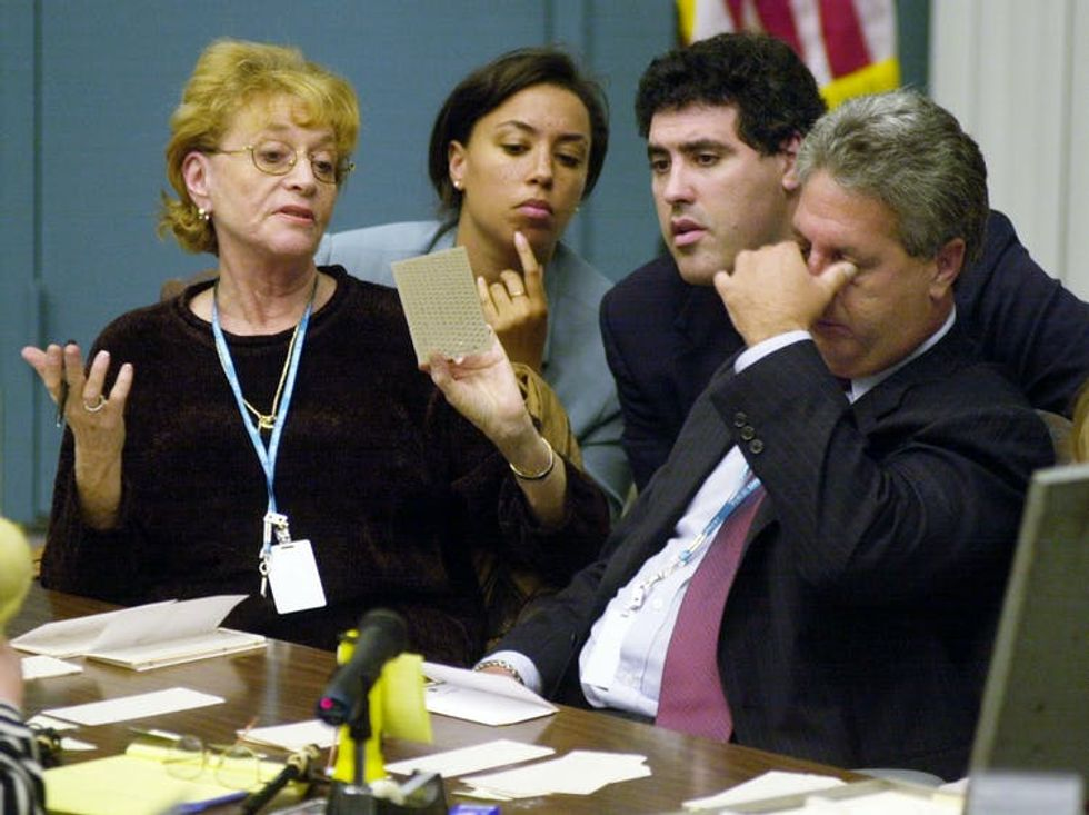People look closely at a Florida ballot in 2000