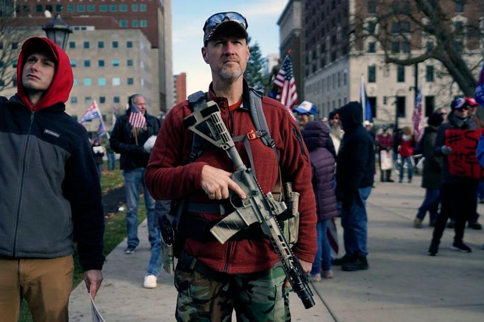 A man carries an assault rifle.