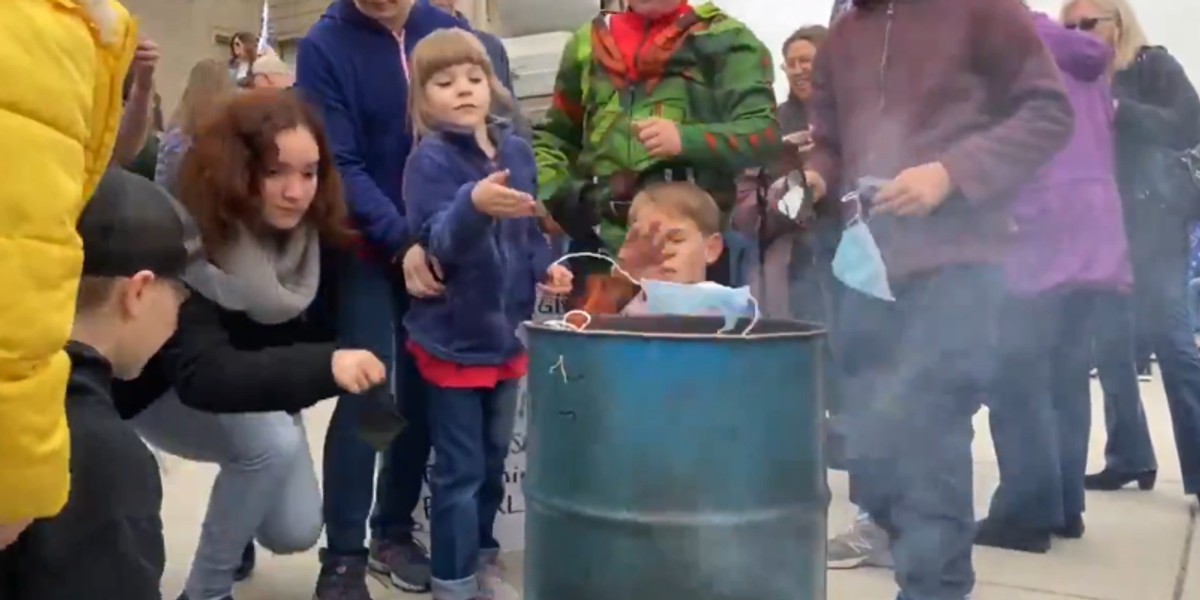 WATCH: Idaho COVID deniers encourage kids to burn their masks on state capitol steps