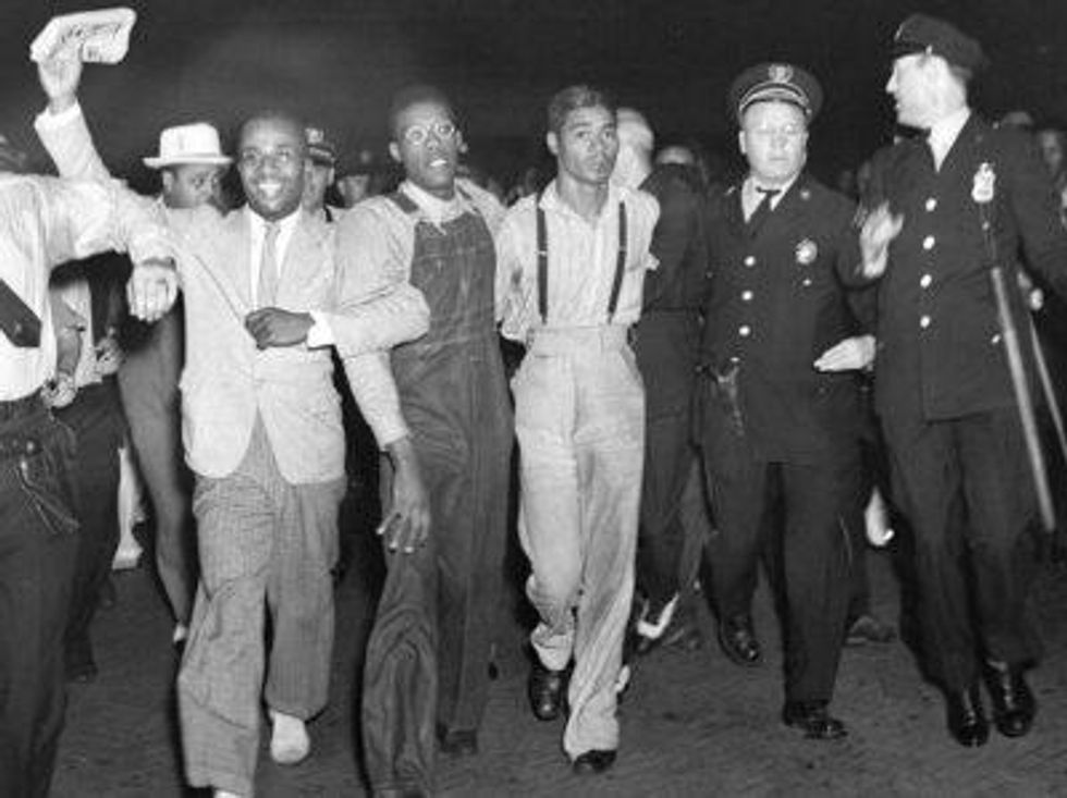 ""\u200bIn this July 26, 1937 file photo, police escort two of the five recently freed """"Scottsboro Boys,"""" Olen Montgomery, wearing glasses, third left, and Eugene Williams, wearing suspenders, fourth left, through the crowd greeting them upon their arrival at Penn Station in New York.""980|733|?|en|2|ede2d76efb89ca6c99a77c1f878796a0|False|UNLIKELY|0.35308387875556946