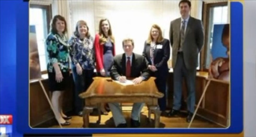 Kansas Gov. Brownback stages weird 're-enactments' of himself signing anti-abortion bill