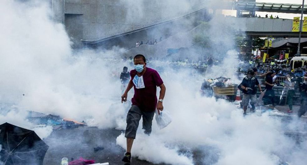 Police use teargas as thousands of pro-democracy demonstrators fill streets of Hong Kong