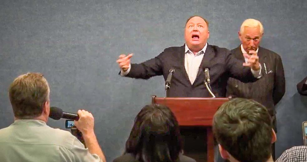 WATCH: Alex Jones goes berserk and molests the American flag when he's asked about his links to Russia