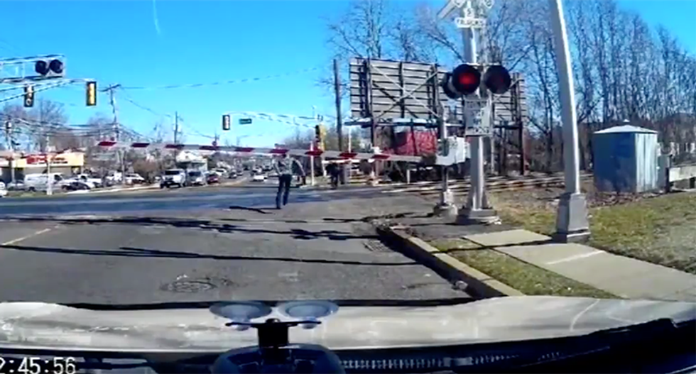WATCH: Driver leaps from car to save elderly woman from oncoming train